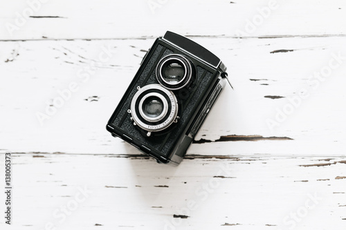 Poster Retro medium format camera on wood table background, vintage concept