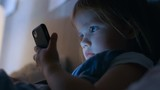 Cute Little Girl Watches Cartoons on a Smartphone. Shot on RED EPIC-W 8K Helium Cinema Camera.