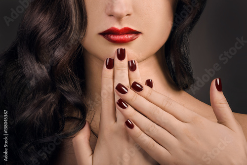 female fingers with vinous manicure and ombre lipstick close up Poster