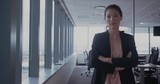 Beautiful female executive standing in office with her arrms crossed. Happy business woman at work.