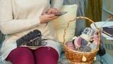 Girl photographs needlework on a smartphone