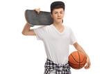 Teenage boy holding a skateboard and a basketball