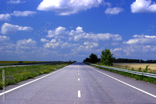 Asphalt road over blue sky background.  Poster