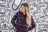 cheerfull teenager in a graffiti wall.