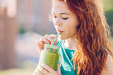 red hair woman drinking with a straw a healthy green juice