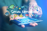 Concept of man holding smartphone with social network title and multimedia icons flying around