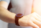 Hand holding black smartwatch with technology screen