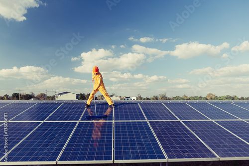 Technicians are cleaning solar panel. Poster