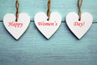 Happy Women's Day.Decorative white wooden hearts on a blue rustic wooden background.
