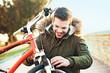 Young man checking brake on bike