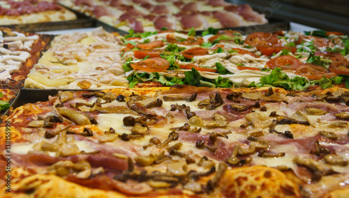 traditional italian pizza with various vegetables, mushrooms and meat at the window of italian pizzeria in Bergamo, Italy