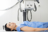 Female Patient Lying Under X-ray Device In Examination Room