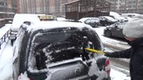 Woman in black jacket cleans a car from the snow brush