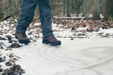 Shoes of hiker standing on frozen puddle in forest.