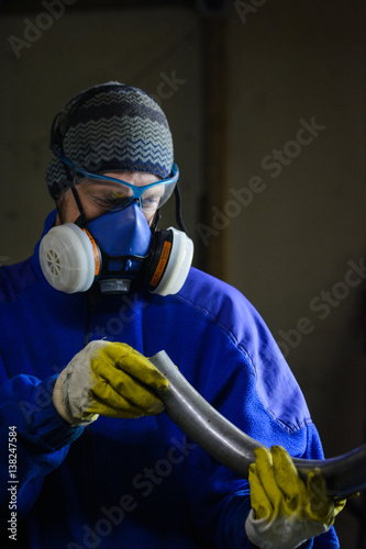 Young man in an industrial background, quality checking a piece of bent steel tube-pipe Poster