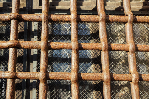 Poster Close up iron bars or metal grating on window or prison cell