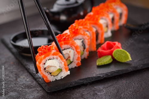 Aluminium Sushi bar Japanese cuisine. Salmon sushi roll in chopsticks on a stone plate over concrete background.