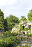 Romantic summer garden, with white wisteria growing on old, ruined stone house, by a lake .