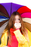 Woman under umbrella sneezing in tissue