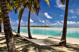 Stunning view of a beach in the lagoon of Aitutaki, Cook Islands, in the South Pacific Ocean. Clear water, palm trees, a white sand beach and a large hammock between palm trees on a sunny day. - 138277146