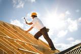 roofer or Carpenter working on Roof on construction site backlit - 138301337