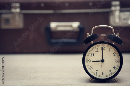 Poster retro style image of alarm clock showing nine with vintage suitcase on the background