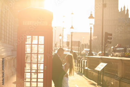 Groom and bride near a phone cabin in London Poster
