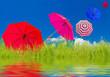 parasols couleurs emportés par le vent, fond herbe et ciel bleu avec reflets