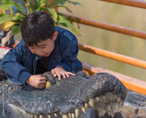 Staande foto Kameleon boy play with crocodile doll