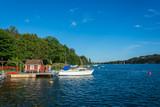 En brygga ute i Stockholms skärgård med en vit båt förtöjd
