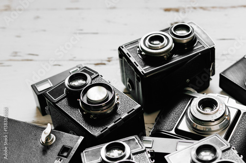 Poster old vintage retro photo cameras on white wooden background