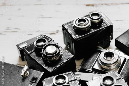 old vintage retro photo cameras on white wooden background