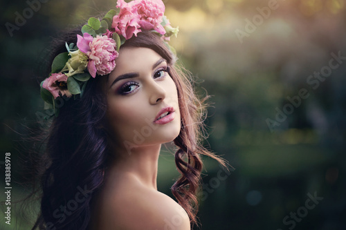 Beautiful Woman with Flowers Wreath Outdoors. Sunset in Summer Garden