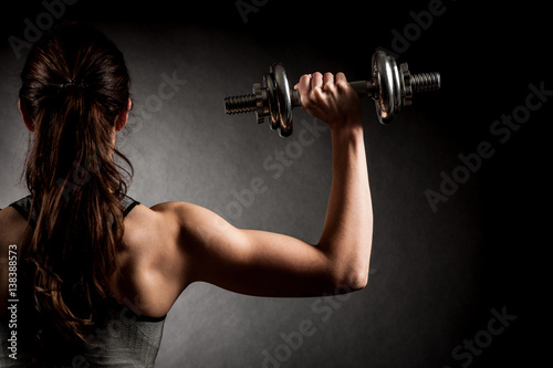 Atractive fit woman works out with dumbbells as a fitness conceptual over dark b Poster