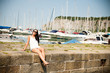 young woman with summer dress and sunglasses rests on stone pier of marina on hot summer day