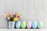 Fototapety Easter eggs and a spring bouquet of tulips on a wooden table.