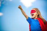 Funny little girl plaing power super hero over blue sky background. Superhero concept. - 138402100