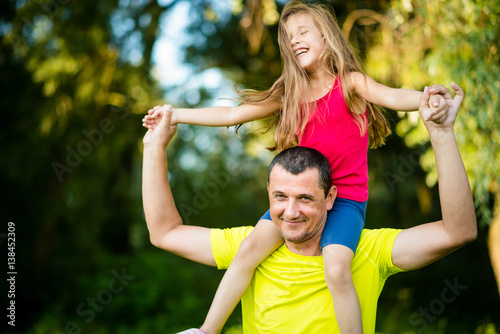 Mature parent carrying girl child on his shoulders. Fatherhood. Poster