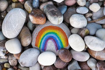 Rainbow painted on pebble with stones background
