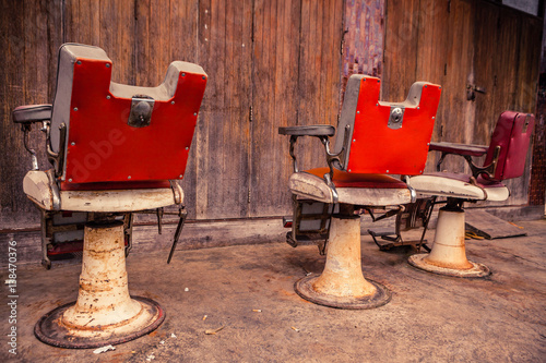 Group of old barber chairs on wooden background.
