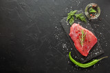 raw beef steak with rosemary and peppers on dark stone