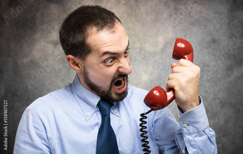 Businessman yelling at his phone in his office