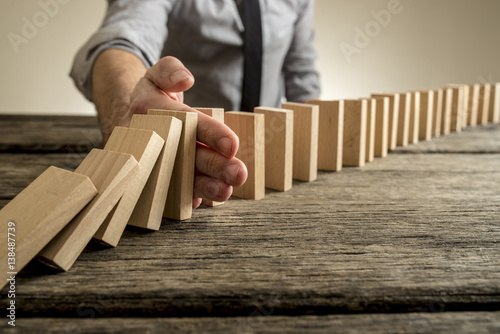 Poster Man stopping domino effect on wooden table