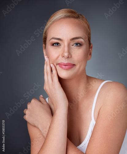 Leinwanddruck Bild woman smiling looking to the camera touching her cheek