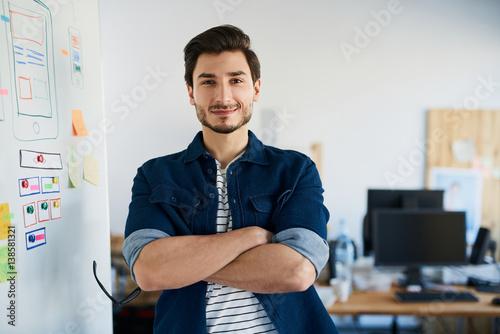 Poster Portrait of happy web designer standing in office