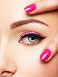 Closeup woman face with pink nails near eyes.