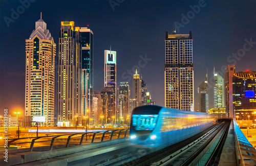 Self-driving metro train with skyscrapers in the background - Dubai, UAE Poster