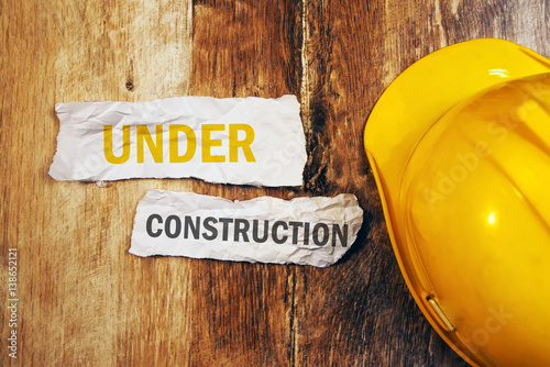 Under construction concept with protective yellow hard hat helme