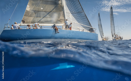 Fotobehang Zeilen Blue sailing boat on the sea with keel under water