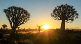 Happy successful winning woman arms up between trees at sunset
